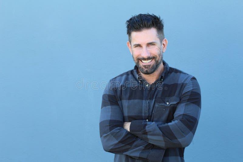 笑英俊的成熟的人微笑和,当横渡他的有拷贝空间的时胳膊 免版税库存照片