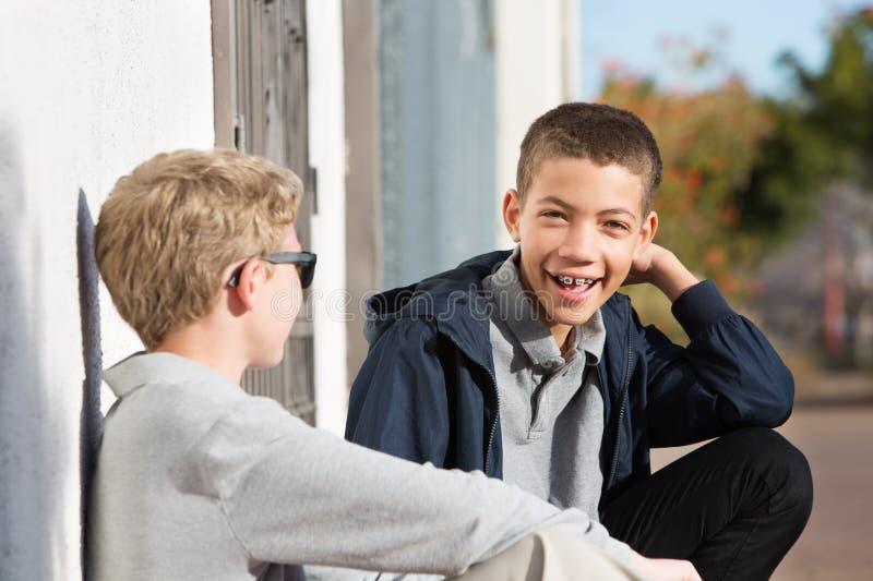 笑青少年与外面括号与朋友 免版税库存照片