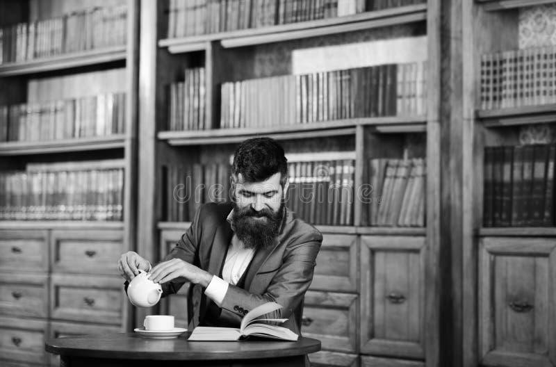笑,放松,乐趣,休闲,爱好概念 愉快的人在内部的葡萄酒坐并且享受松弛读书 博若莱红葡萄酒 免版税库存图片
