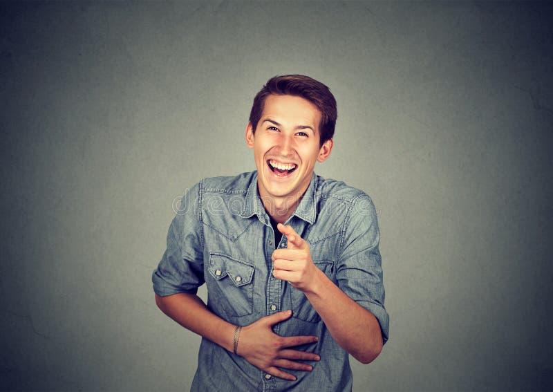笑年轻人的画象指向与手指 库存照片
