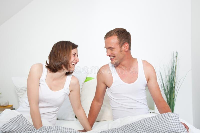 笑年轻愉快的夫妇,当坐在床上时 免版税库存图片