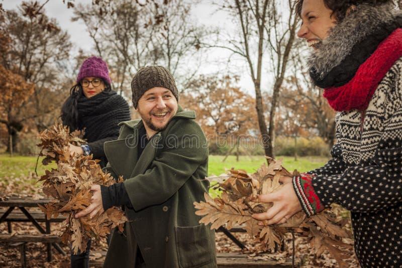 笑画象的人获得与秋叶的乐趣 免版税库存照片