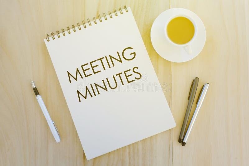 笔、一杯咖啡和笔记本顶视图写与会议备忘录在木背景 免版税库存图片