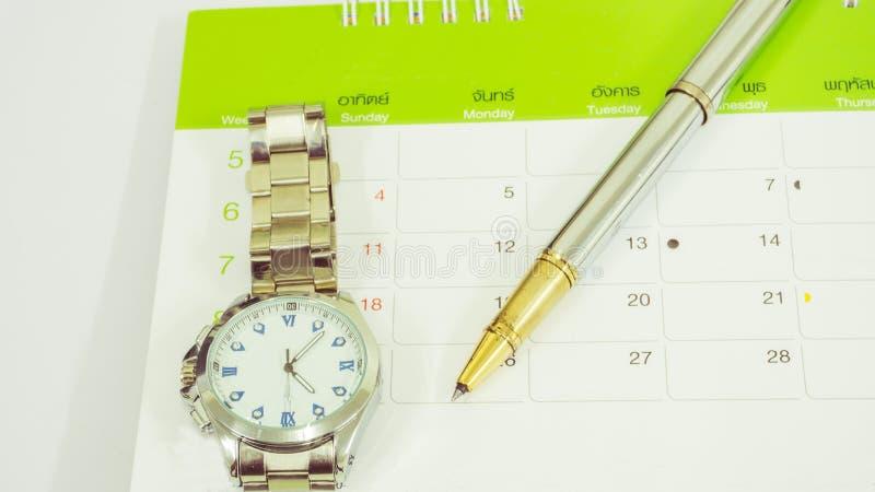 笔、手表和日历在白色桌上 免版税图库摄影