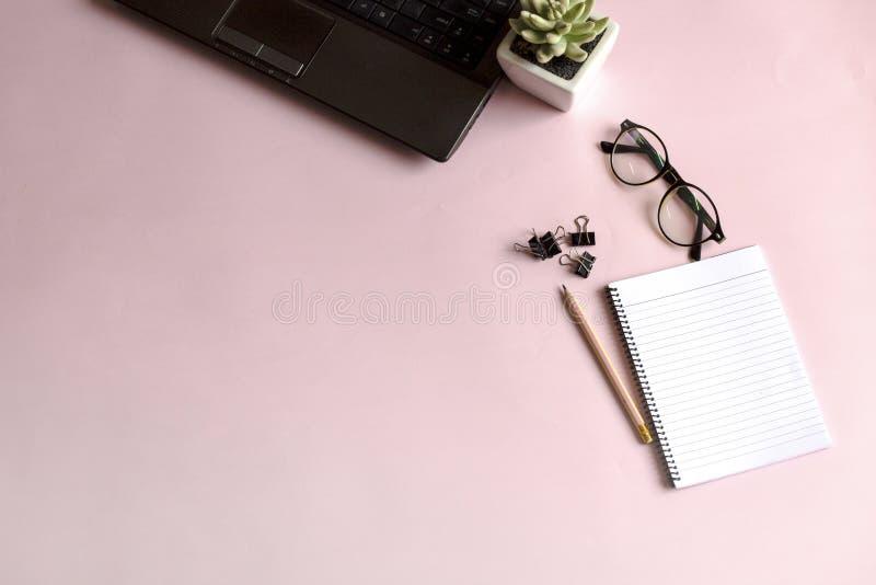 笔、玻璃和笔记本在桃红色背景 免版税库存图片