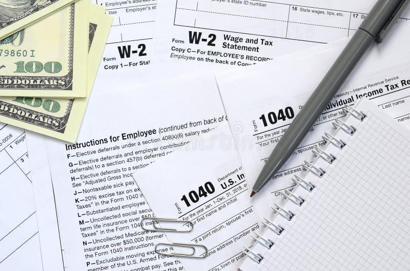 笔、笔记本和美金是在报税表的谎言1040 免版税库存照片