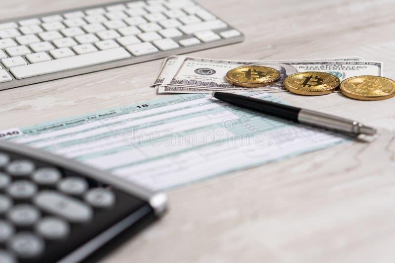 笔、bitcoins、美金和计算器在报税表1040 U 在键盘旁边的S 单独所得税 库存图片