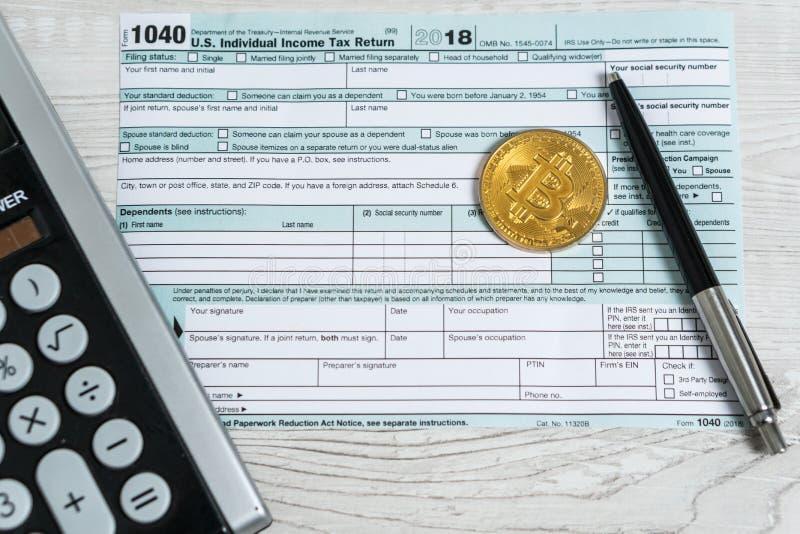 笔、bitcoins和计算器在报税表1040 U S 单独收入税单 时候缴纳税 库存照片