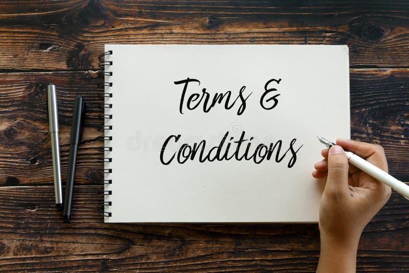 笔和手候宰栏文字在笔记本的顶视图期限和条件在木背景 免版税库存照片