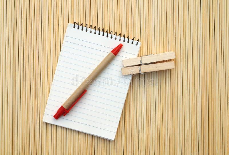 笔和笔记薄在竹暗淡 库存照片