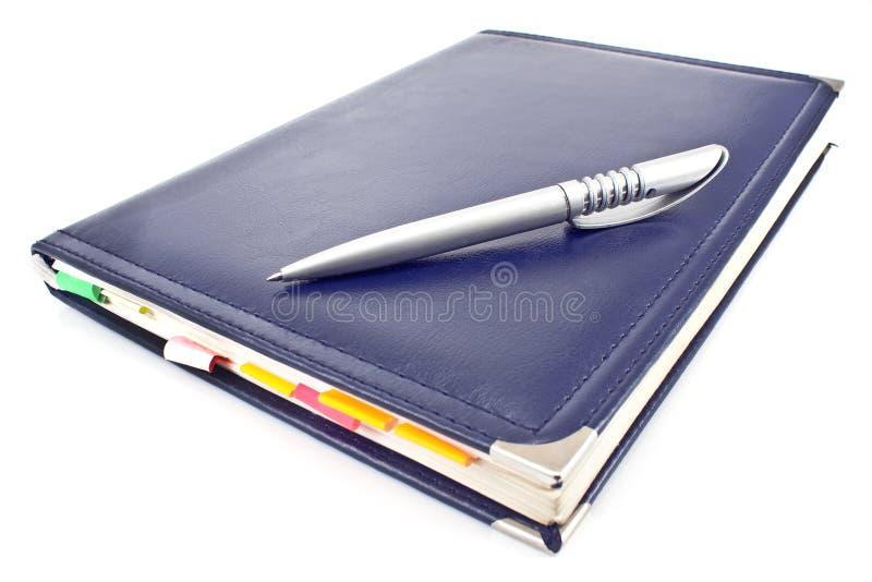 笔和蓝色笔记本 库存图片