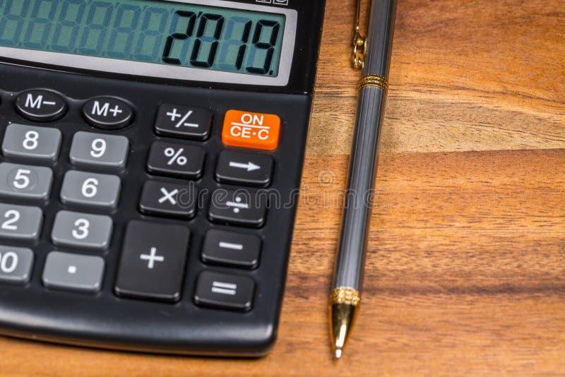 笔和计算器有2019数字的在显示在木表上在木表上 免版税图库摄影