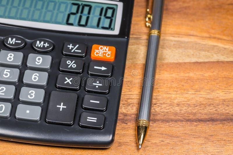 笔和计算器有2019数字的在显示在木表上 库存照片