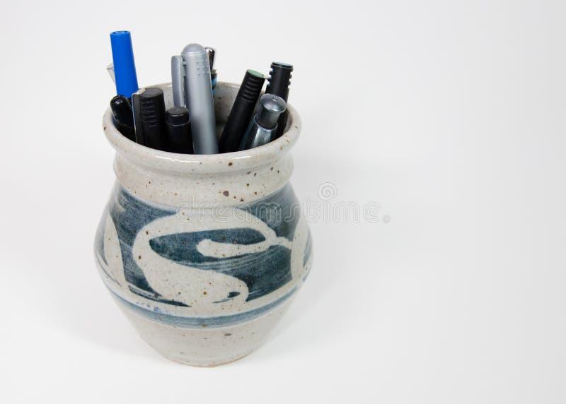 笔和铅笔在粗陶器杯 库存照片
