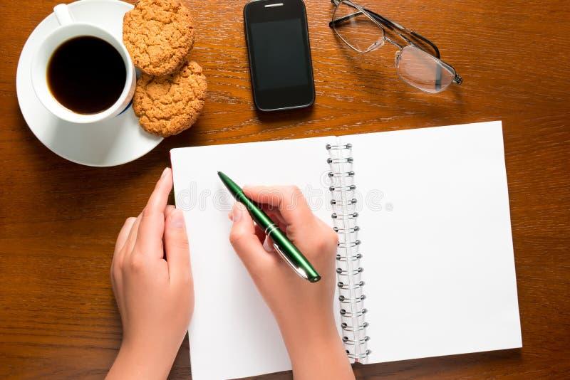 笔在女性手和一个开放笔记薄上 免版税图库摄影