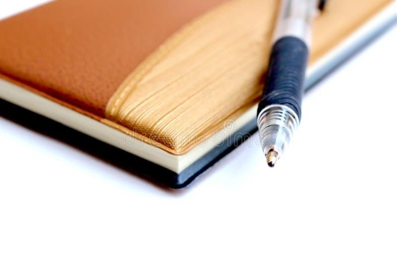 笔特写镜头在棕色笔记本的 免版税库存照片