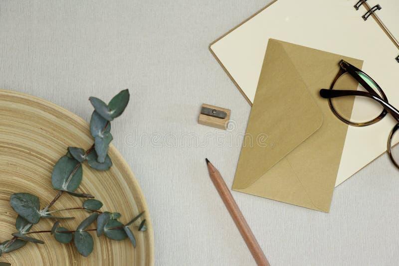 笔记本、木铅笔&磨削器,信封,眼镜,在篮子的玉树分支 免版税库存照片