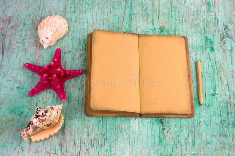 笔记本、海壳的铅笔和汇集,夏天启发背景 图库摄影