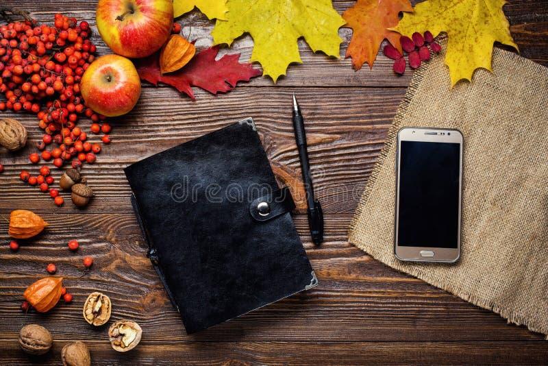 笔记本、笔和电话在秋天静物画,秋天离开, g 免版税库存图片
