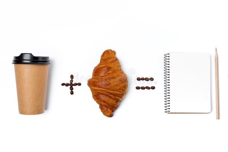 笔记本、纸在白色背景隔绝的咖啡杯和新月形面包 免版税库存照片