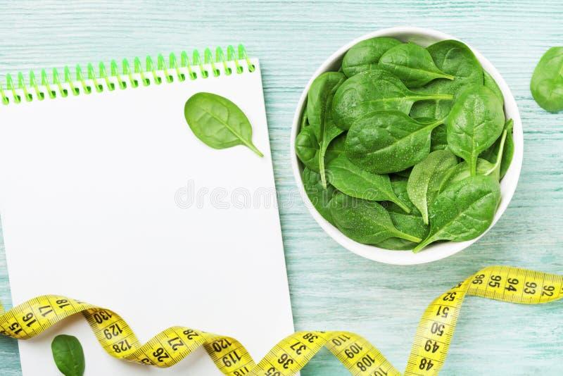 笔记本、绿色菠菜叶子和卷尺在木台式视图 饮食和健康食物 免版税图库摄影