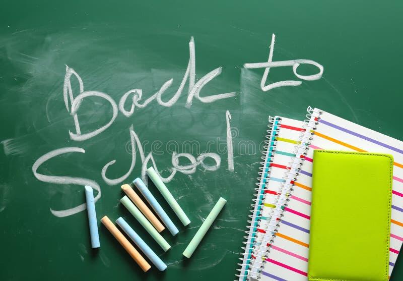 笔记本、蜡笔和词回到在黑板写的学校 库存图片