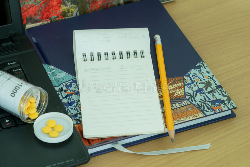 笔记本、铅笔、药片在被打开的瓶和膝上型计算机 库存图片