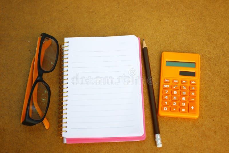笔记本、镜片和计算器在木背景财政概念的 库存图片
