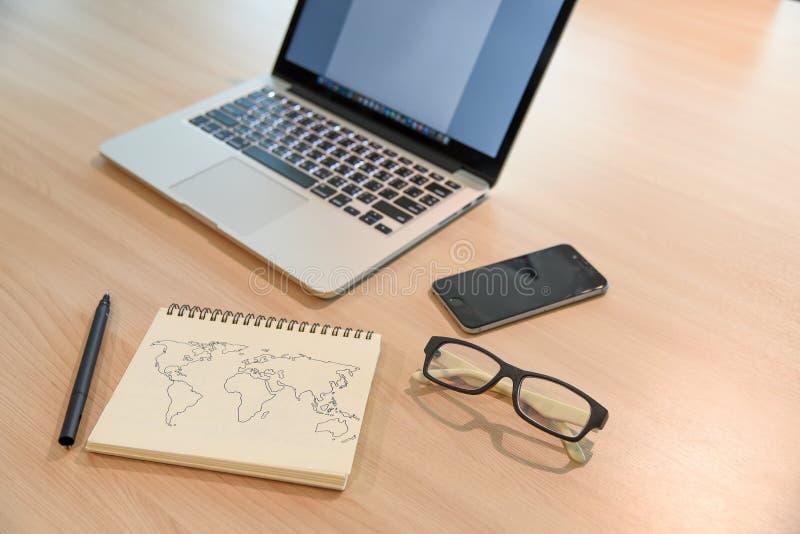 笔记本、玻璃、智能手机和膝上型计算机在办公桌上 库存照片