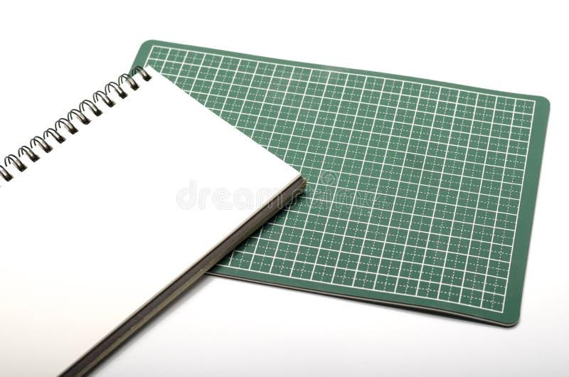 笔记本和切口席子 库存图片