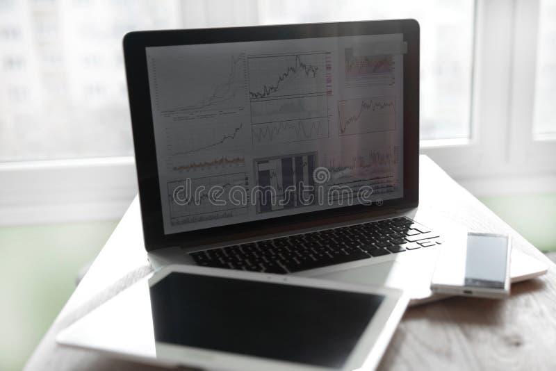 ?? 笔记本和数字片剂的模糊的照片在工作场所 免版税库存照片