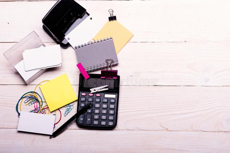 笔记本和穿孔机在笔附近在白色木背景 库存照片