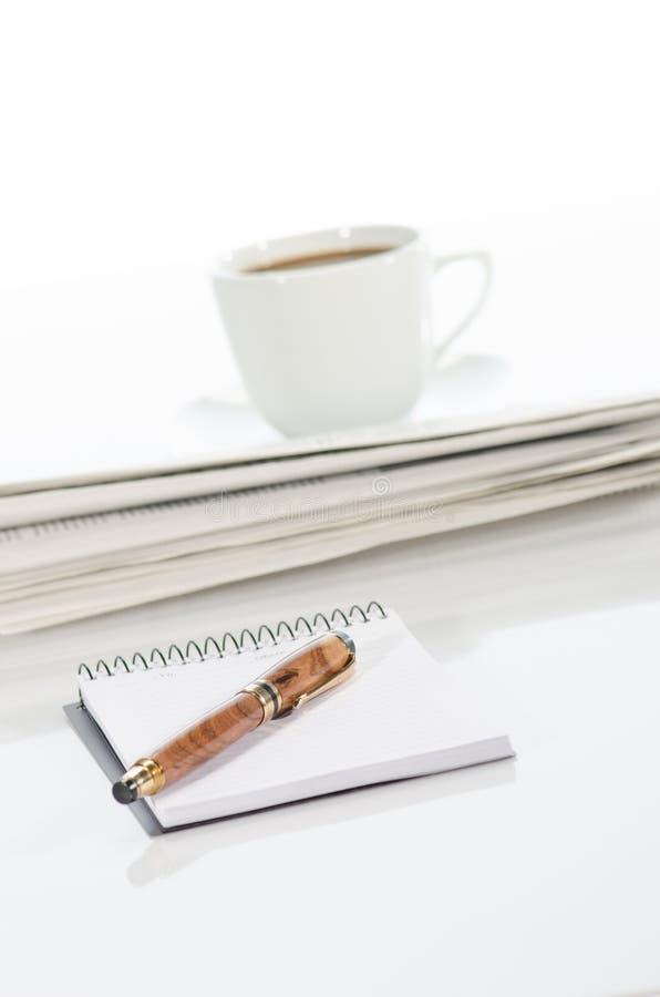 笔记本和笔、咖啡和报纸 免版税库存照片