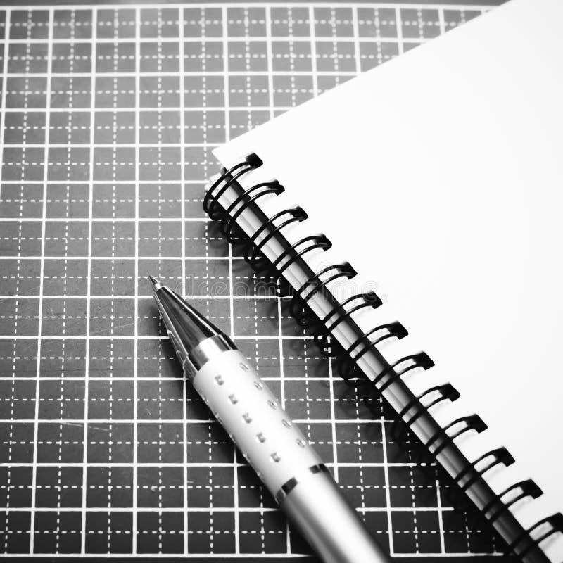 笔记本和笔在切口席子黑白颜色定调子样式 库存照片
