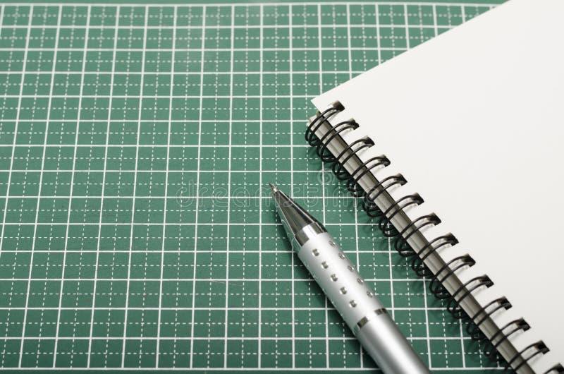 笔记本和笔在切口席子 免版税库存照片