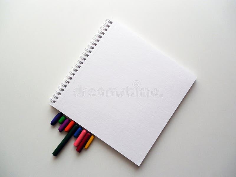笔记本和色的蜡笔在白色 库存照片