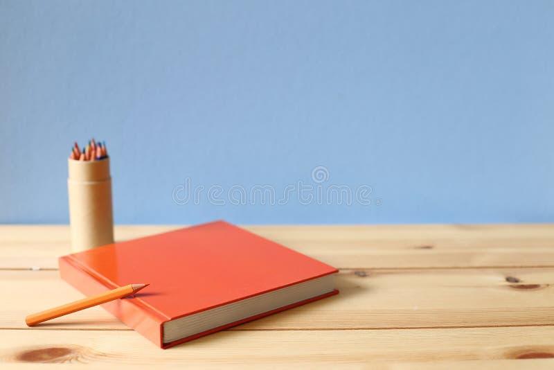 笔记本和色的铅笔在木书桌上 库存图片