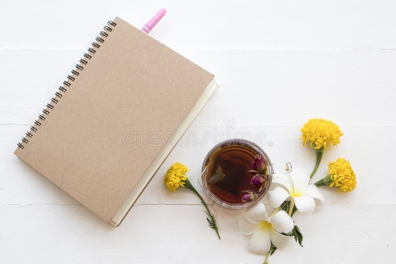 笔记本和草本健康饮料热的玫瑰色茶鸡尾酒水 图库摄影