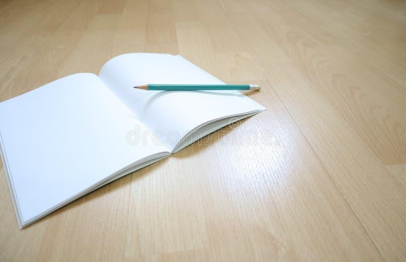 笔记本和铅笔在木地板上 图库摄影
