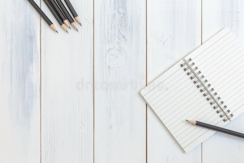 笔记本和铅笔在木桌,顶视图,工作场所,办公用品,背景的概念上 免版税库存图片