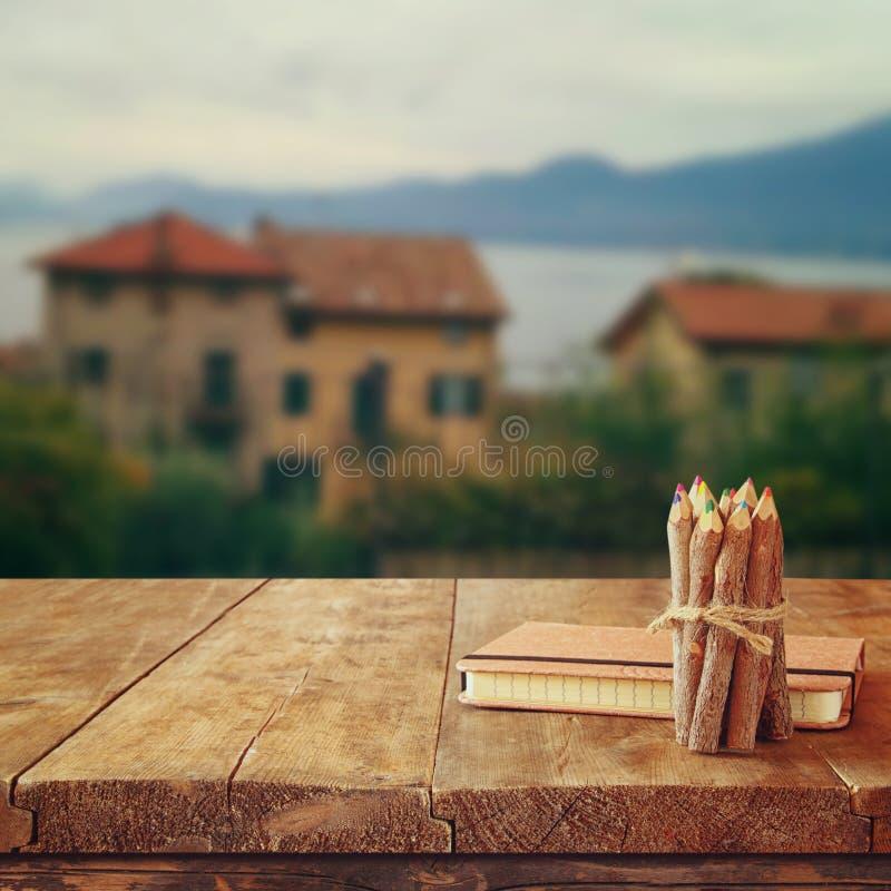 笔记本和铅笔在老木桌上在浪漫普罗旺斯农村风景前面 减速火箭的被过滤的图象 库存图片