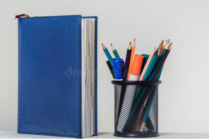 笔记本和铅笔有标志的在立场 库存照片
