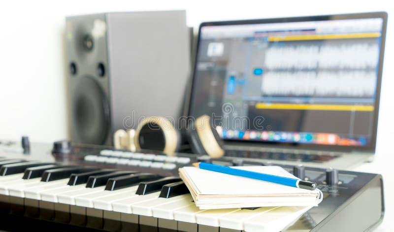 笔记本和音乐键盘在音乐演播室桌面上歌曲作家的 库存图片