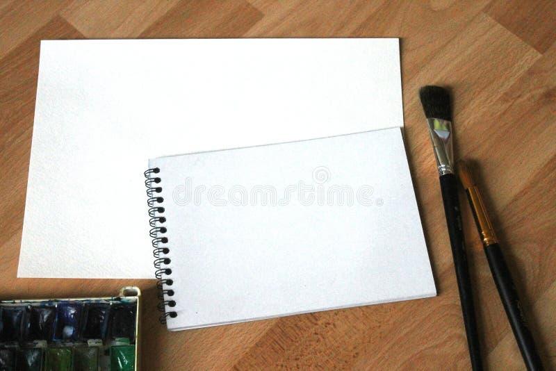 笔记本嘲笑为与水彩油漆的艺术品,调色板,杯水和油漆刷 艺术性的工作工具 库存图片