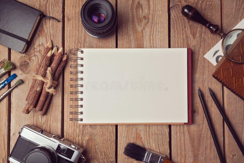 笔记本嘲笑为艺术品或商标设计介绍与影片照相机和透镜 在视图之上 免版税库存图片