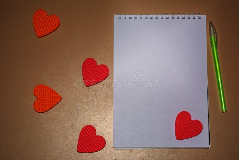 笔记本在桌上说谎在绿色把柄旁边 免版税库存照片