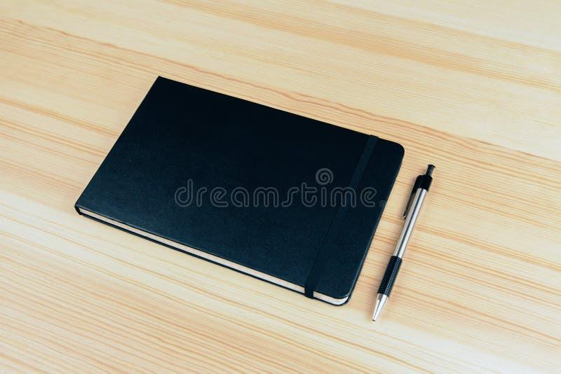 笔记本封口盖板有笔的在木桌上 库存例证