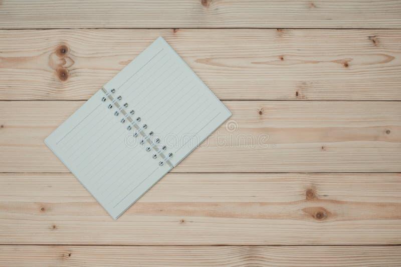 笔记本或倒空在木台式视图的白皮书与拷贝s 免版税库存照片