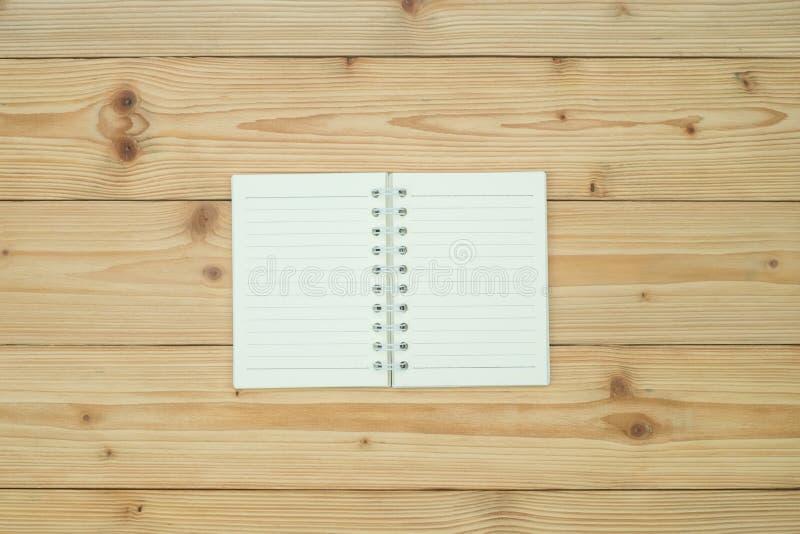 笔记本或倒空在木台式视图的白皮书与拷贝s 库存图片