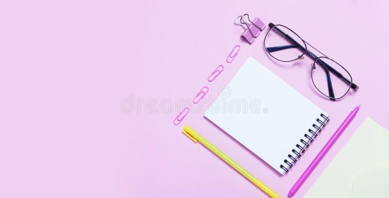 笔记本或笔记薄与眼睛玻璃和耳机在桃红色backgriund 创造性的简单派档案馆概念 顶视图,平的位置 库存图片